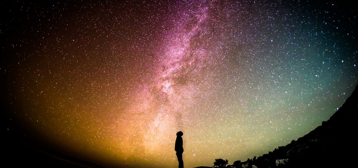 Distant Silhouette Of A Man Looking At Milky Way Galaxy